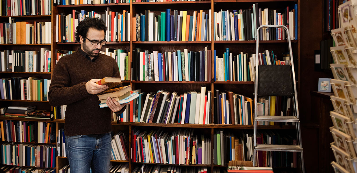 A man in front of a bookcase