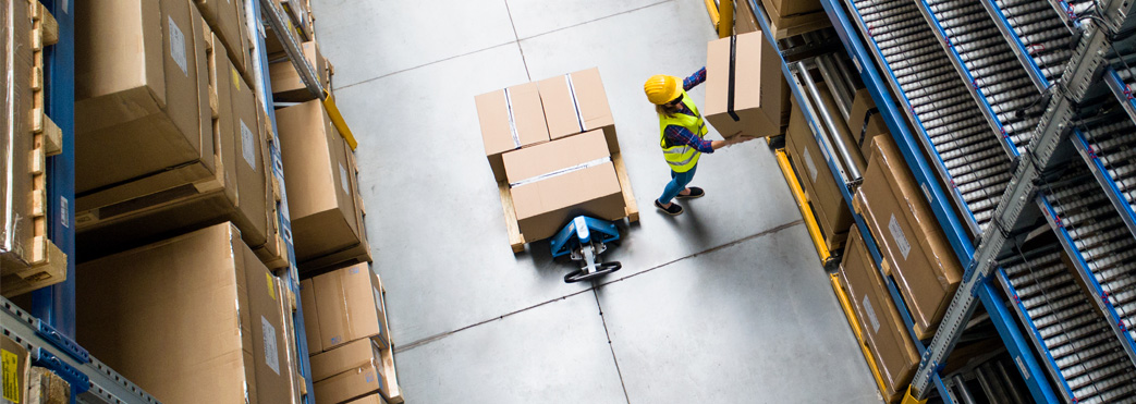 Image of a worker moving boxes in a warehouse
